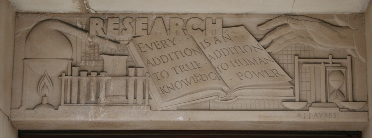 """Research"" and ""Every addition to true knowledge is an addition to human power"" and ""A.J.J. Ayres"" are carved in sand-colored stone above black double doors. A hand and chemistry equipment are also part of the carving."