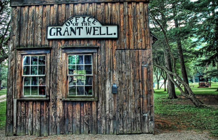 """An rustic, old wood building nestled among the trees. Sign on the front of the building reads """"Office of the Grant Well."""""""