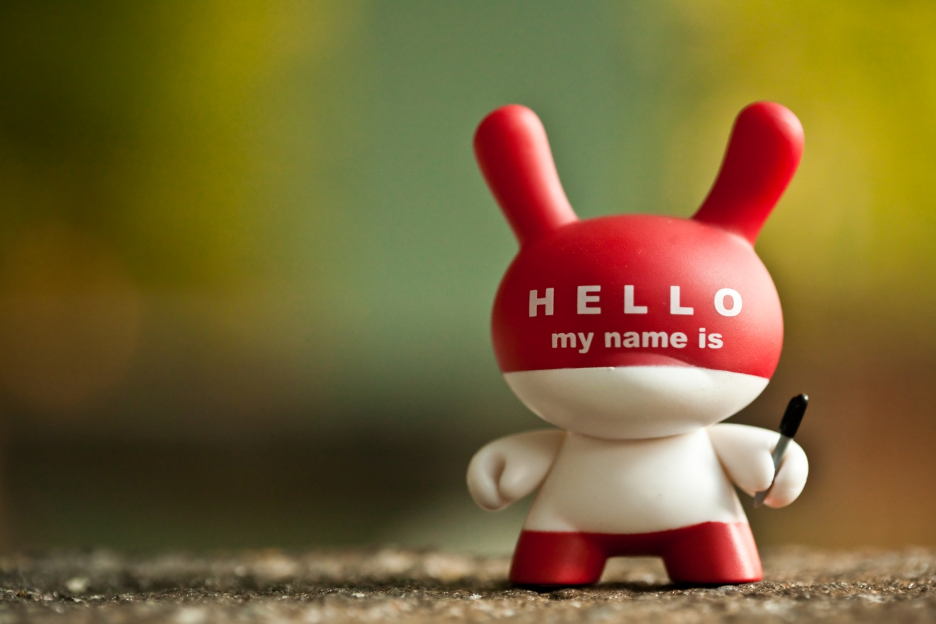 "A vinyl figure of a human-like creature with long ears sticking up from its head has the iconic ""Hello my name is"" graphic look applied to it. The figure holds a black permanent, Sharpie-like marker in its left hand."