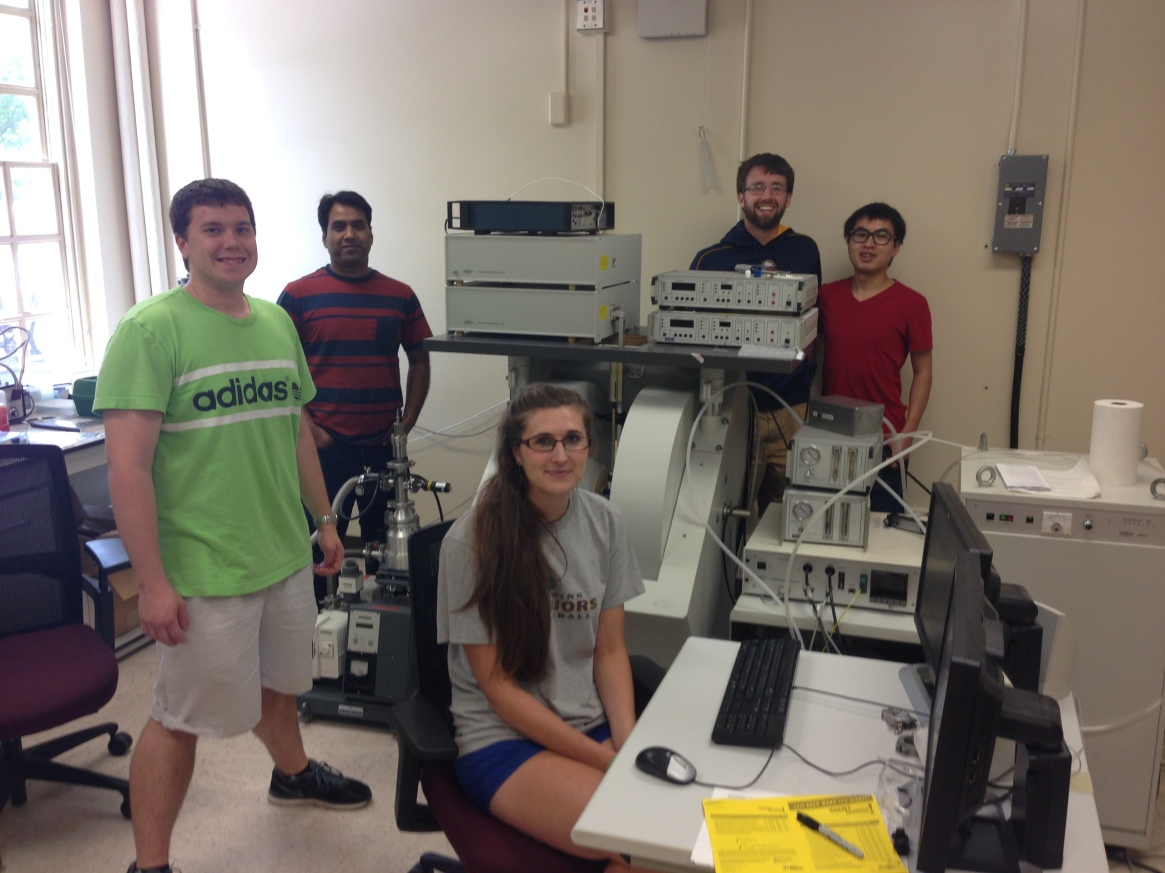 Four graduate students and a postdoctoral researcher pose with equipment they use to conduct research