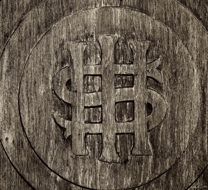 A dollar sign with three vertical lines is carved in the center of a circle, which is placed on top of two other concentric circles. All are carved in rustic-looking wood.
