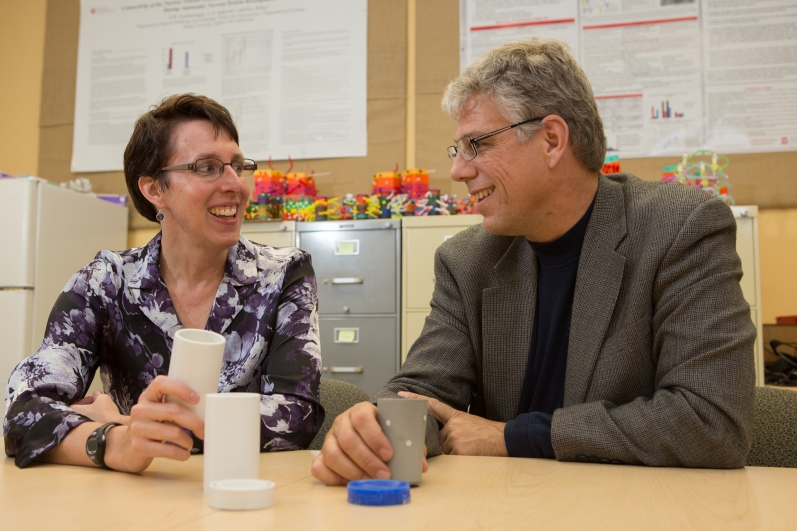 A woman and a man sit at a table in an office. Between them on the table are parts of their invention -- two opaque white cups, an opaque grey cup with small holes on its surface, an opaque white screw-on lid, and a royal blue screw-on lid. File cabinets with various brightly colored toys are in the background.