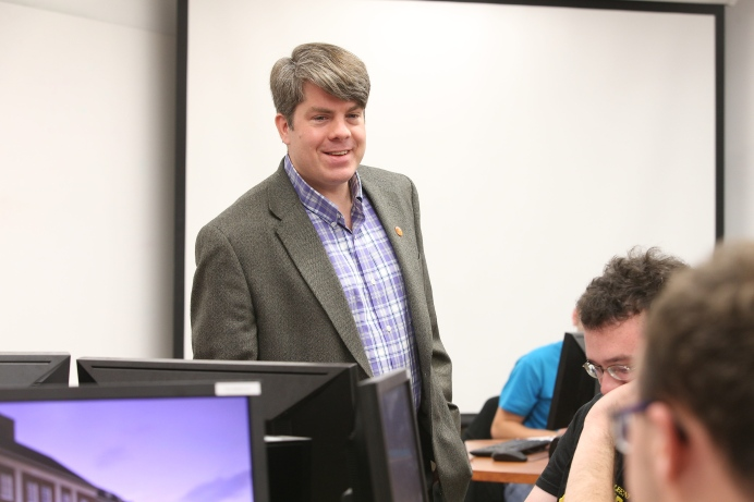 A man wearing a purple plaid shirt and a grey suit jacket stands at the front of a computer lab/classroom. Seats in the room are filled by students.