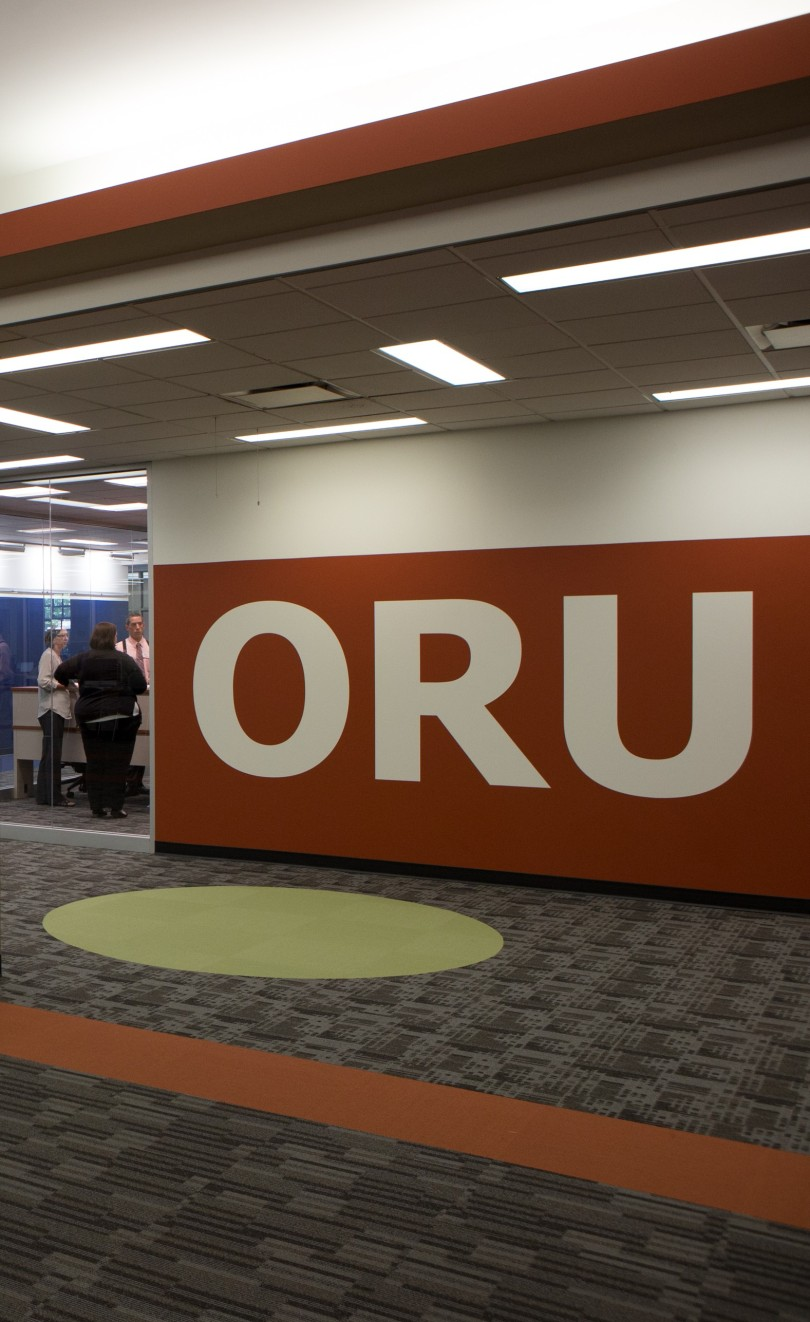 "Image of Miami University's Office of Research for Undergraduates (ORU). Visible are a wall with ""ORU"" painted on it and three people standing in a circle in a glass-walled office."