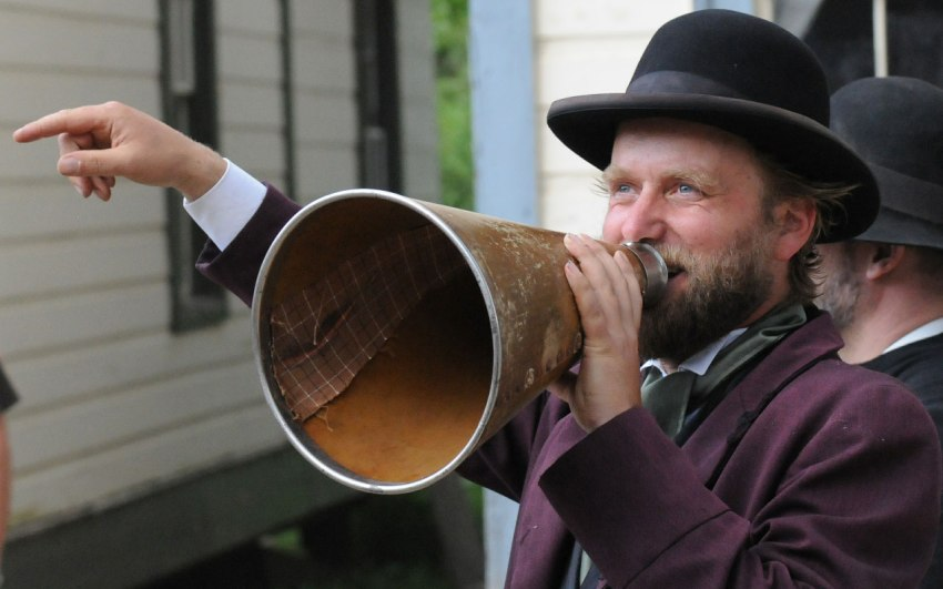 A smiling, bearded man wearing a black bowler hat, an old-fashioned looking purple suit and a grey cravat shouts into a battered cardboard megaphone while pointing out of the frame with his right hand.