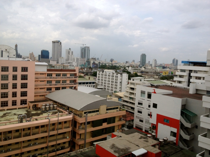 A variety of buildings is packed typically close in this view of the Bangkok skyline. Shorter 5- to 10-story buildings in the foreground include two orange brick buildings and three white buildings. Tall skyscrapers are visible in the background, including one with a crane on the roof.