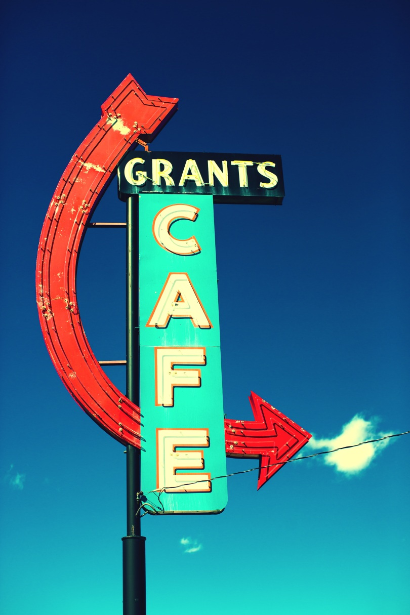 "An old-fashioned neon sign reads ""Grants Cafe."" ""Grants"" is one a black background and appear smaller and perpendicular to the ""Cafe"" part, which appears vertically on an aqua blue background. A Red arrow curves from the ""Grants"" part down ""behind"" the ""Cafe"" part and out the other side. Behind the sign is blue sky and a few small clouds."