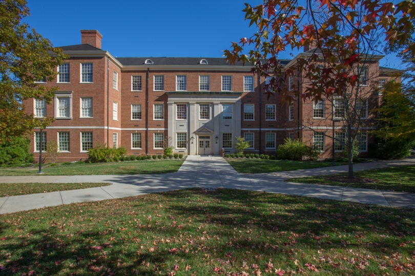 Image is a long shot of a red brick building. The building has two wings, between which is an entrance surrounded with grey stone. Grass, sidewalks and trees with fall leaves are visible in the foreground.