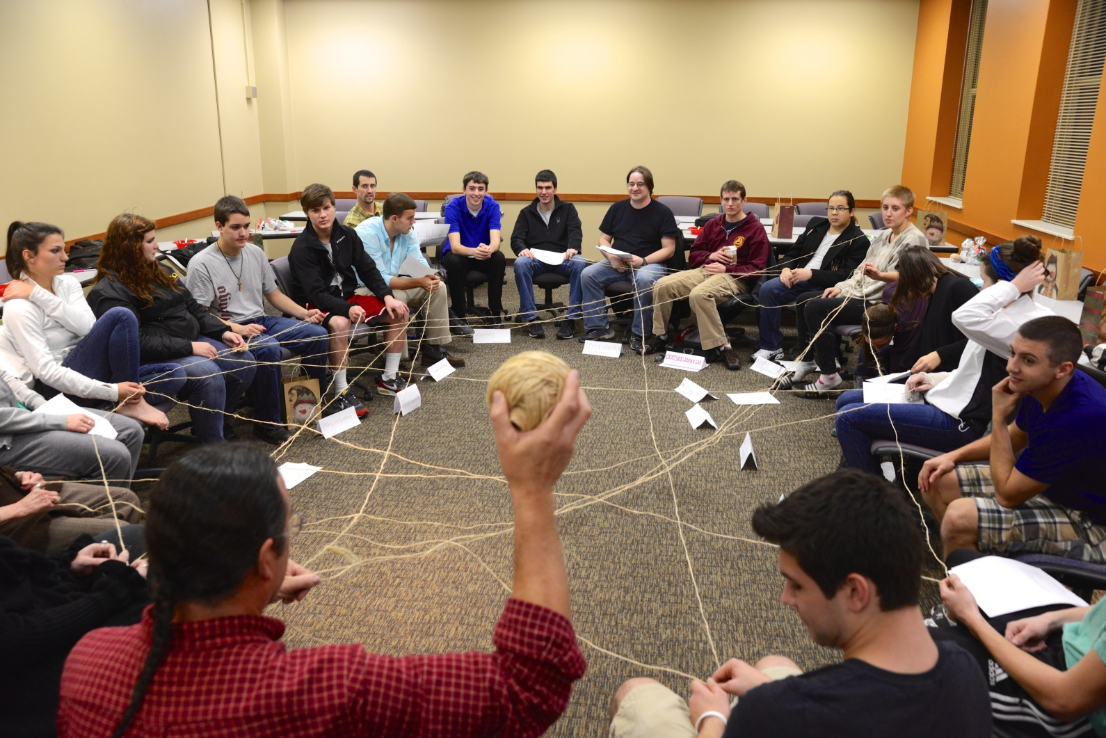 A group of about 20 students sits in chairs in a circle that takes up the whole room. Twine criss-crosses the empty center of the circle, as some students hang onto a piece of it. In the foreground, a man in a red plaid shirt, whose back is the the camera, holds a ball of twine up in the air with his right hand.