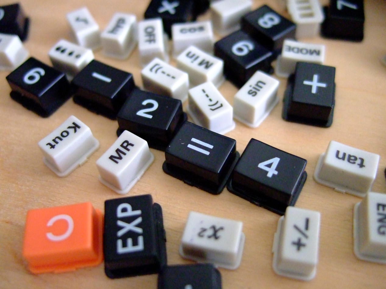 """Keys of various sizes from a disassembled calculator are scattered on a woodgrain surface. Keys with discernible text include the square root key, """"OFF,"""" """"cos,"""" """"X,"""" """"8,"""" """"7,"""" """"6,"""" """"/', """"M in"""" """"MODE,"""" """"+,"""" """"sin,"""" """"[(---,"""" """"tan,"""" """"+/-,"""" the exponent key, """"EXP,"""" """"C,"""" """"MR,"""" and """"K out."""" Arranged in the center, is are the keys that form the number sentence, """"6-2=4."""""""