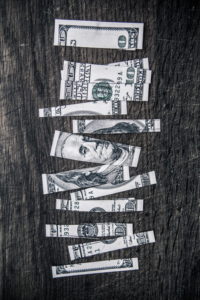 A one hundred dollar bill is cut into 13 strips of varying widths. The strips are arranged on a scarred, dark grey wood background.