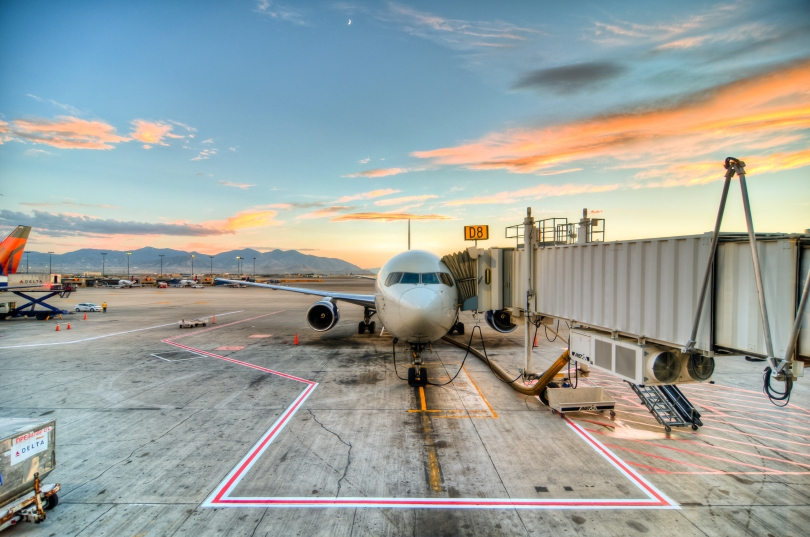 A jetliner is pulled up to a jet way. Visible in the background is the tarmac, other planes, luggage carriers, and other equipment. Far in the distance, mountains are visible. It appears to be sunrise because while the frame is not entirely lit up, the sky is blue and some thin clouds are glowing pretty shades of peach and yellow.