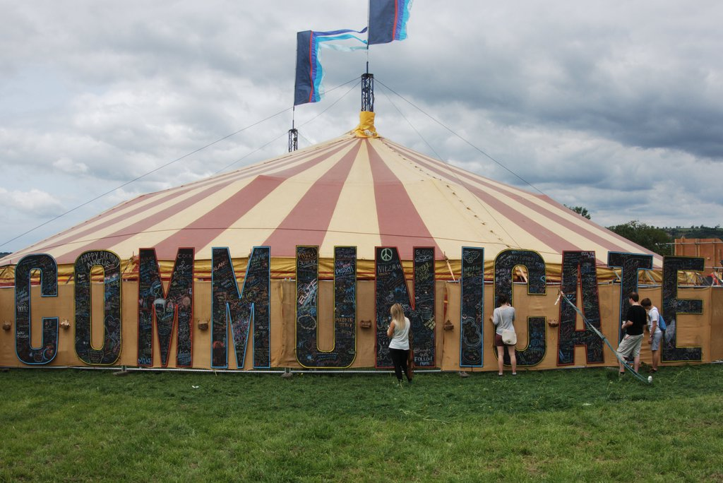 "A yellow circus-type tent, with a yellow-and-red striped roof takes up the frame. On the side of the tent -- in letters taller than the height of the tents' side walls -- the word ""COMMUNICATE"" is spelled out in black letters. Other words and drawings have been doodled on the letters of the word ""COMMUNICATE."" Four people are shown facing the word ""COMMUNICATE,"" and some of them appear as though they may be writing or drawing on some of the letters."