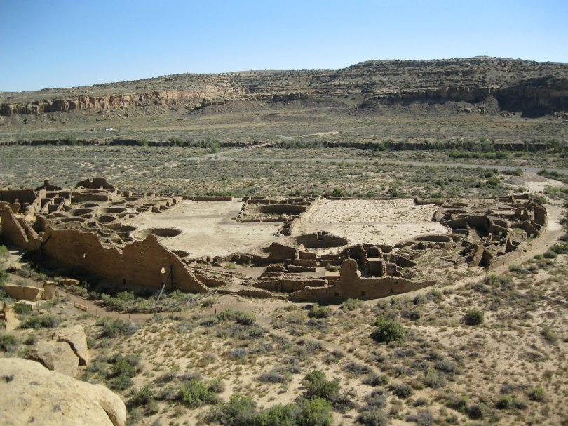 Overhead view of a dessert landscape, with a cliff in the far distance. In the foreground are ruins of Pueblo Indian dwellings. A half circle is open toward the cliffs in the distance. Several round pits or indentations are visible in the ruins, as are what look like walls that would have been between rooms or buildings. A taller wall appears to have spanned the backs of the dwellings.