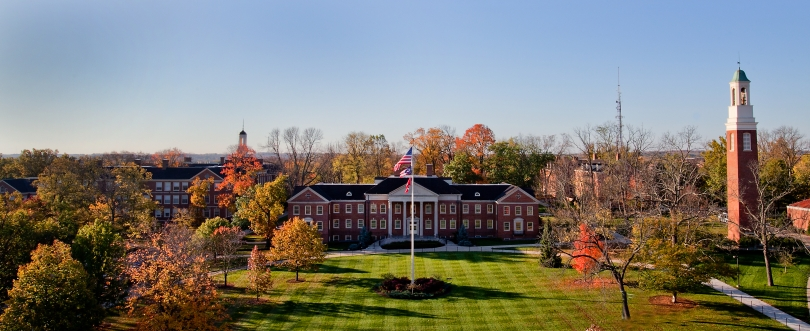 A panorama shot of the campus of Miami University, in Oxford, Ohio. In the center of the image is Roudebush Hall, a 3-story brick building with a columned portico. To the left of Roudebush Hall, Upham Hall, a taller red brick building is visible through the trees. To the right of Roudebush Hall are the Beta Bells, a red brick bell tower with a cream-colored cupola topped by a weathered copper cap and weathervane. A lush green lawn and trees with fall foliage can be seen throughout the image. A flagpole with an American flag, the Ohio state flag, and a Miami University flag can also be seen in front of Roudebush Hall.