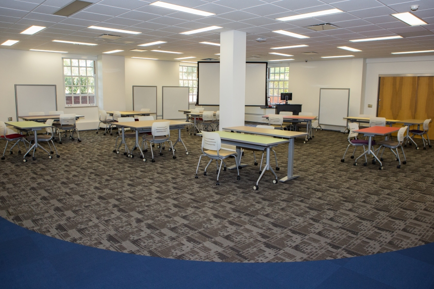Image of instructional space. Ten tables are situated at various positions throughout the room. Each table has several chairs around it. Four portable whiteboards are arranged along the far walls, interspersed between and beside the three windows. A projection screen and teaching station with a computer monitor are also located along the far wall.
