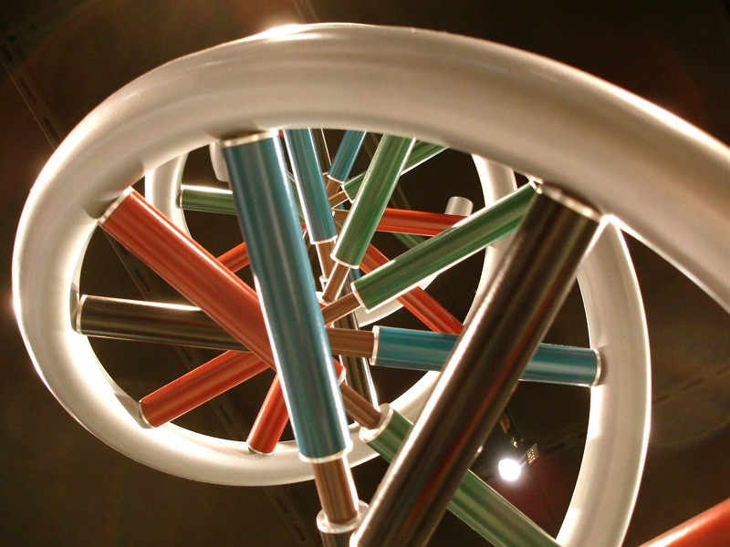 "Giant model of the DNA double helix at a science museum in Ann Arbor. The helixes sides are pearlescent white tubes that twist in toward the center of the frame from the middle left. The ""rungs"" between the sides are red, blue, green and brown tubes connected by slimmer copper-colored tubes."
