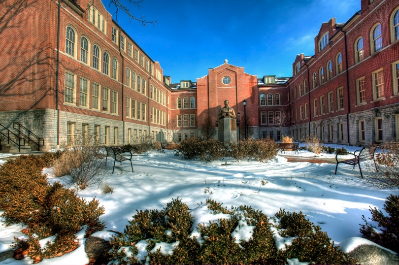 A brick and stone building surrounds three sides of a snow-covered courtyard. In the center of the courtyard is a bronze-like bust on a concrete pedestal. The bust depicts a man reading a book. The courtyard also contains benches, shrubs, and a walking path.