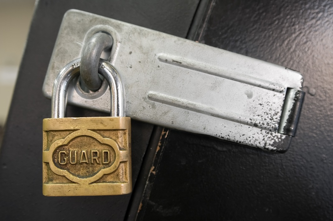 "A brass lock with a silver loop and the word ""GUARD"" stamped on its face secures a silver hasp on what appears to be a door, which is painted black."