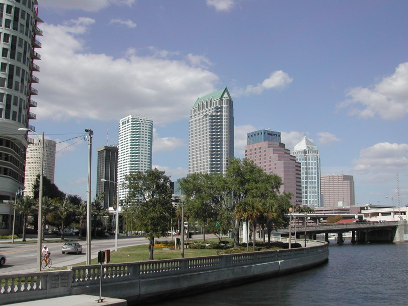 Photo of Tampa, Florida skyline as viewed from Bayshore Boulevard. In the right front of the frame is a river. A bridge over the river is visible in the background. In the left front of the frame, a road runs along the river. A bicyclist is riding on the sidewalk toward the viewer, while two cars are driving on the road in the opposite direction. A small grassy area with a few trees and other plantings is between the road and the river. A tall building with several balconies is partially visible at the far left of the image. Seven other multi-story buildings are visible in the background.