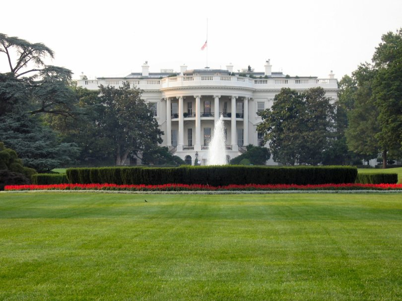 Photograph of the south side of the White House. The flag on the pole on the roof of the White House is at half-staff. A fountain is active in front of the white house, there are leaves on the surrounding trees, and a row of red tulips runs in front of the bushes framing the fountain.