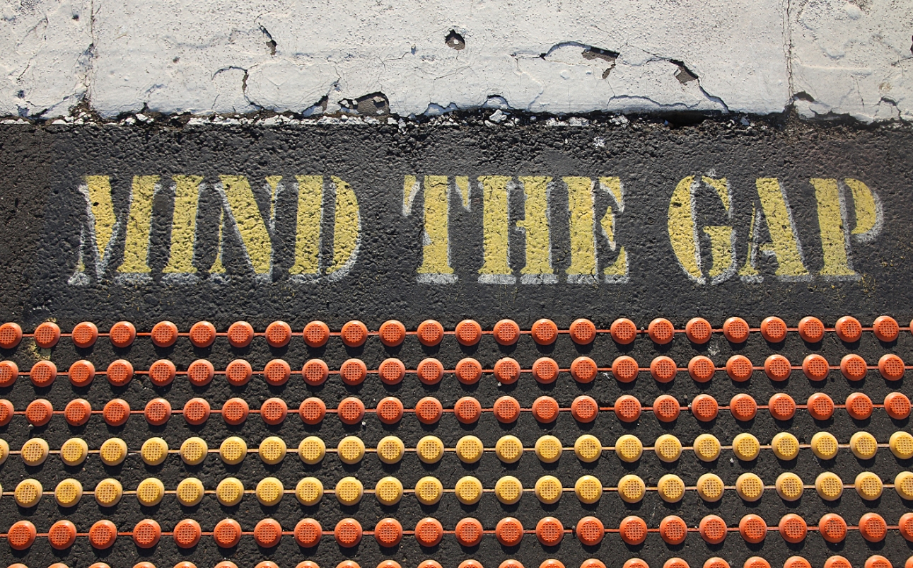 "A wide strip of white-painted pavement appears at the top of the frame. Under that the words, ""MIND THE GAP"" are painted on the pavement. Below those words, there are seven rows of dots, which are perhaps reflectors, connected horizontally on a strip. The first three rows are orange, the next two are yellow and the last two are orange."