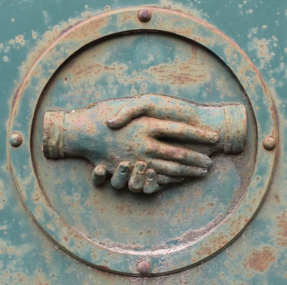 Two hands clasping each other, as though shaking in greeting, are reverse embossed on a rusty metal surface. The metal surface is painted a green-blue that seems to be wearing off in places, where the rust is taking over. The hands are encircled by a raised metal ring that has metal rivets at the 12-, 3-, 6-, and 9-o'clock positions.