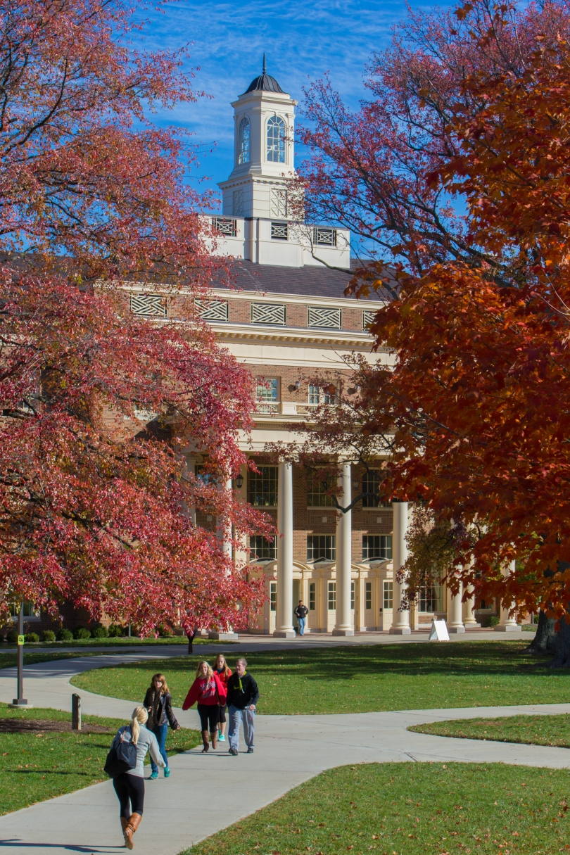 A red brick building with cream trim is visible between two trees with fall foliage. The building is four or five stories tall, with big columns in the front and a cupola on top. Several people are walking on the sidewalk in front of the building. Green manicured lawns are also visible in front of the building.