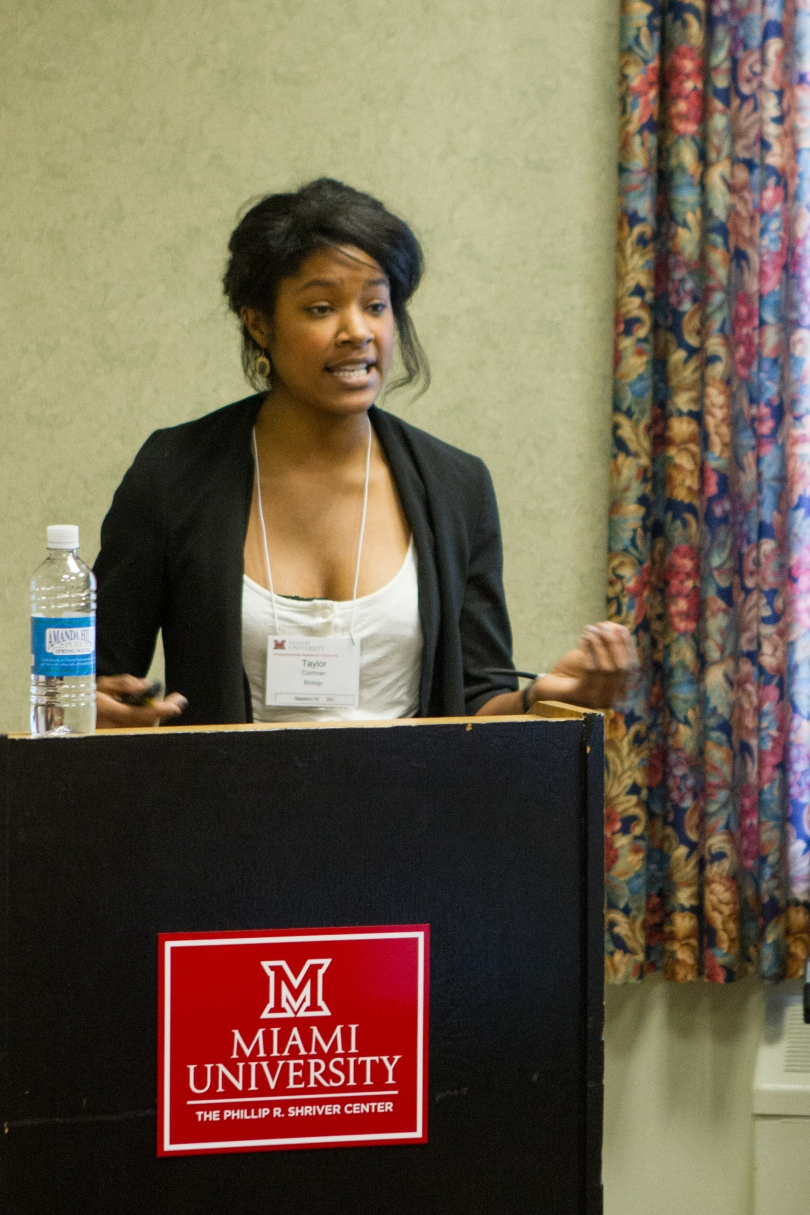 "In this photograph, a young African-American woman stands behind a podium. She is speaking and gesturing. She holds a remote control in her right hand and a bottle of water sits on the podium. The plaque on the front of the podium is embossed with the Miami University logo, above the words, ""The Phillip R. Shriver Center."" Floral curtains hang at a window to the woman's left."
