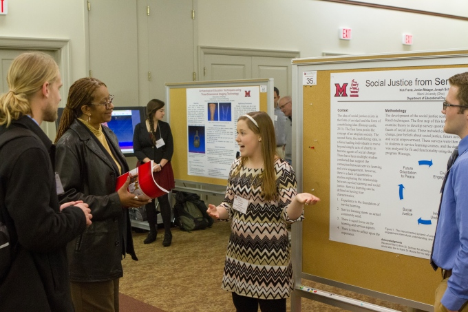 "In this photograph, four people are standing in front of a research poster pinned to a portable bulletin board. At the left of the frame are a Caucasian man and an African-American woman. They are listening to the young Caucasian woman in the center of the frame, who is talking and gesturing toward the poster. At the far right, half-visible is a young Caucasian man. The title of the poster is partially visible: ""Social Justice from Service."" The headers ""Context"" and ""Methodology"" are also visible, but the remaining text is too small to read. There is also a diagram on the poster that shows a cycle, with blue arrows pointing from one step in the cycle to the next. ""Future Orientation to Peace"" and ""Social Justice"" are the two steps in the cycle for which the labels are fully legible."