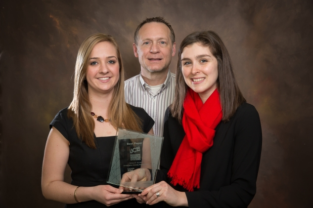 """Two young women hold a glass award. Visible on the award are the words """"Best Paper"""" and """"UCIS."""" Between the two women stands a man who is older than they are. All are smiling."""