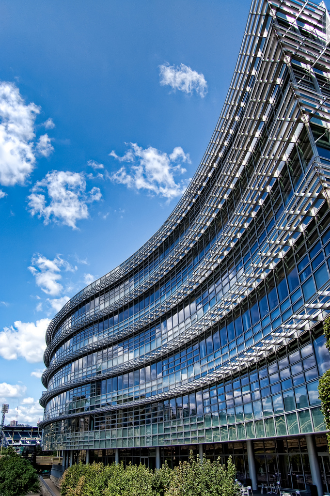 Photograph of the Alcoa Corporate Center in Pittsburgh. The building is made of glass and steel and is sort of wave-shaped. The blue sky and white wispy clouds are reflected in the building's windows.