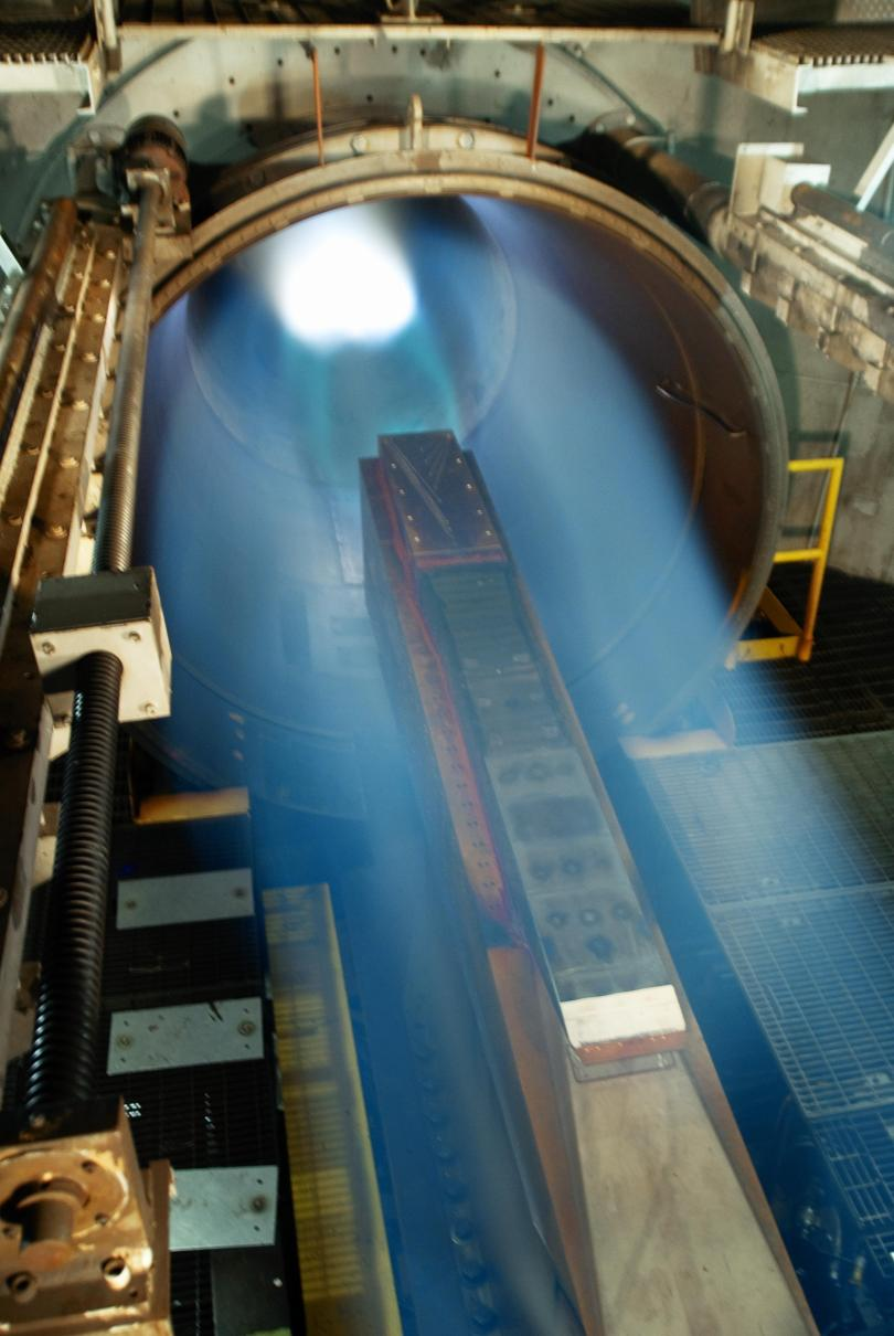 Image of jet engine being tested. A blue, fuzzy column of pale light emanates from a metal cylinder. Within the cylinder and the column of light, a bright white light glows strongly. The metal cylinder is surrounded by other metal parts.