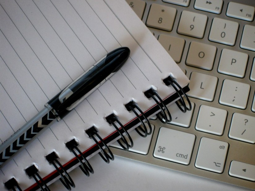 A pen and a spiral bound notebook sit atop a Mac computer keyboard.
