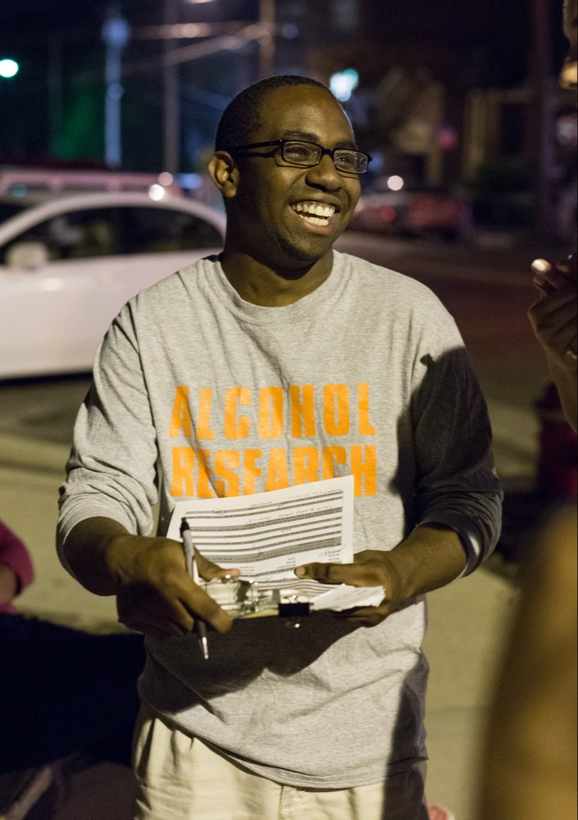 A student wearing a t-shirt that reads, Alcohol Research, holds a clipboard and a pen. He is smiling and talking to someone who cannot be seen in the photo.