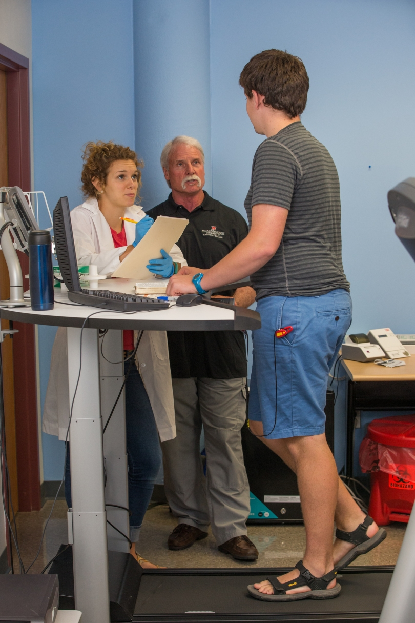 A young man walks on a treadmill attached to a desk. On the desk are a computer, a book, and a travel mug. Standing next to the desk, an undergraduate researcher wearing a white lab coat and blue exam gloves takes notes in a folder while speaking to the man on the treadmill. Behind the undergraduate researcher, her research mentor looks on.