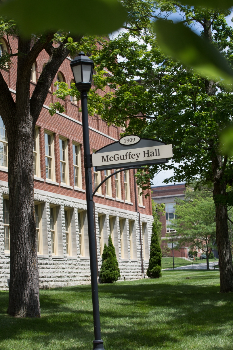 In front of a red brick building, a lamppost bears a sign for McGuffey Hall.
