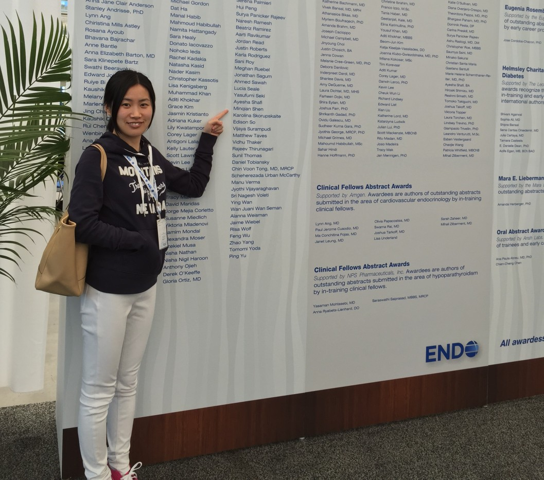 A woman stands in front of a very large poster. She points to her name -- Minqian Shen -- within a long list of names. Visible text: ENDO. 2015 Abstract Awards and Travel Grants. Early Career Forum Travel Awards. Supported by the Endocrine Society. These application-based travel awards are presented to graduate students, medical students, postdoctoral fellows, and clinical fellows in endocrinology. 125 travel awards supported by the Society; 2 additional travel awards supported by Women in Endocrinology.