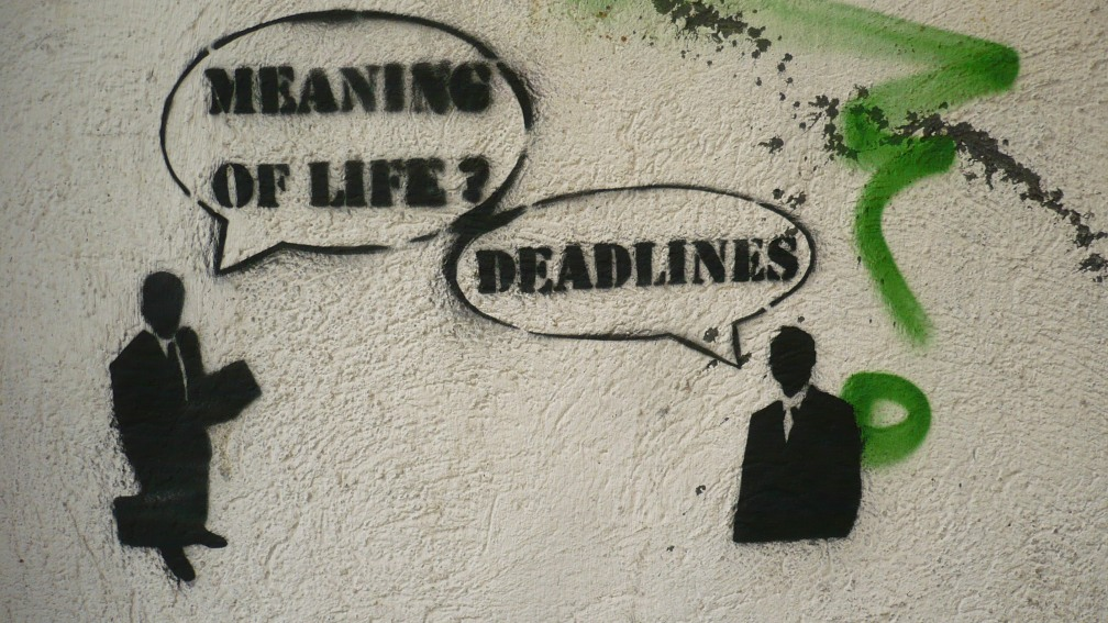 "Graffiti of two suited businessemen. A speech bubble indicates the first man saying, ""Meaning of Life?"" A speech bubble indicates the second man saying, ""Deadlines."""
