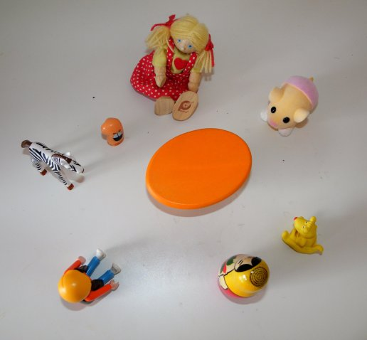 Toys -- a girl soft doll, a mouse stuffed animal, a dog figurine, a Russian nesting doll, a boy action figure, a plastic zebra figurine, and an unidentifiable figurine sit in a circle around a toy table.