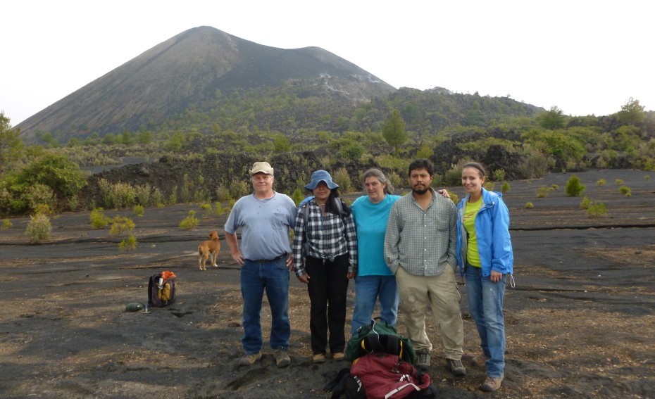 A group of five people stands in a line. A volcano rises behind them in the distance.