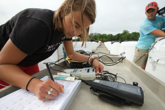 A student transfers information from scientific instruments to a form on a clipboard. In the background, another student is measuring something in a holding tank.