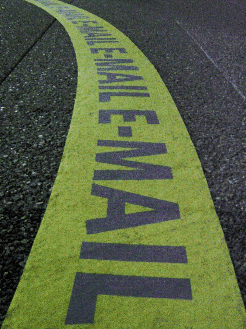 "A yellow stripe on a road is stamped with the word ""E-MAIL."""