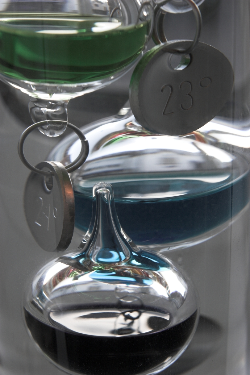 Close up of parts of a Galileo thermometer. Tags on two of the globes read 23 degrees and 24 degrees, respectively.