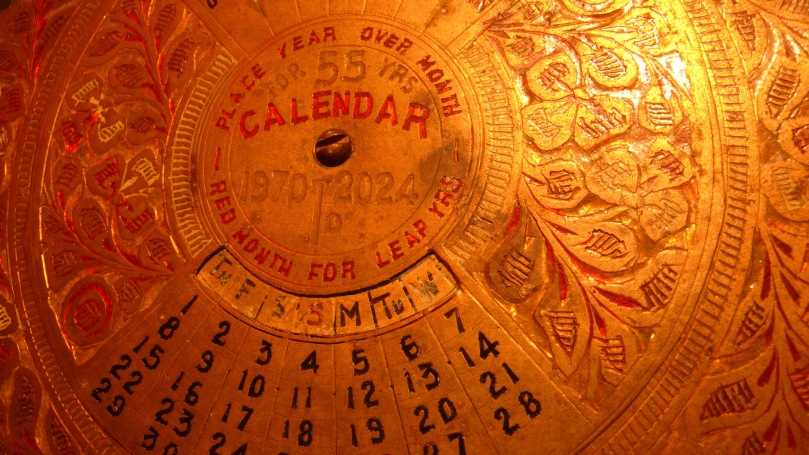 Round, metal perpetual calendar. Text: Place Year Over Month. For 55 Yrs. Calendar. 1970-2024. Red Month for Leap Year. Th F S S M Tu W. 1 2 3 4 5 6 7 8 9 10 11 12 13 14 15 16 17 18 19 20 21 22 23 24 27 28 29 30
