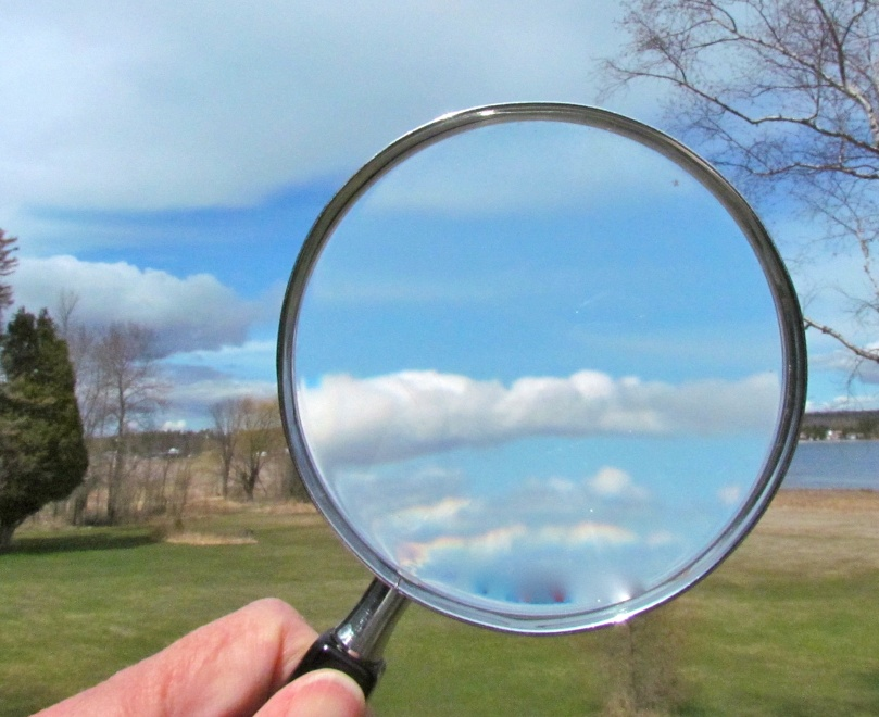 A hand holds a magnifying glass up to the sky. In the glass, clouds are magnified. Visible in the background are more sky, trees, grass, and a body of water.