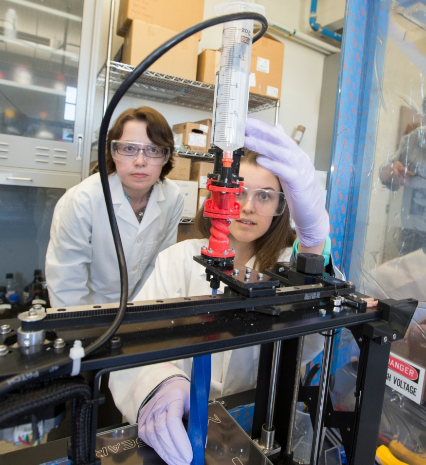 A student uses 3D printing equipment while her professor supervises.