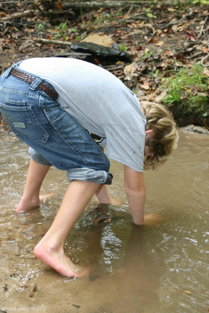 A kid with his pants rolled up to the knees is wading in a creek. He's bent over, with his hands in the water, like he's picking something up.