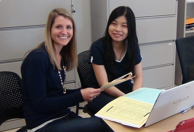Lauren Fussner and another person sit at a table reviewing paper documents and consulting a laptop.