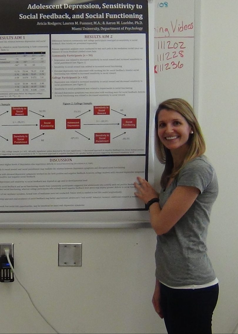 Lauren Fussner stands beside a poster describing her research on adolescent depression, sensitivity to social feedback, and social functioning.